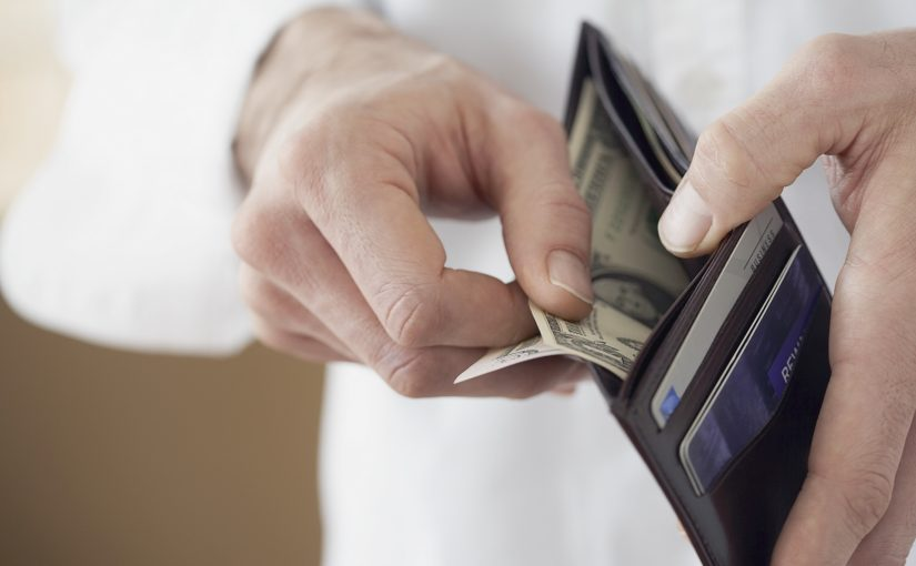 Man Taking US Currency Out of Wallet --- Image by © Fancy/Veer/Corbis